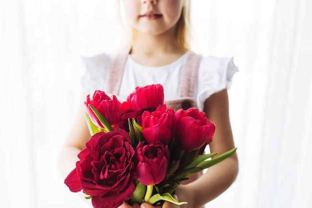 Meisje met boeket van rode tulp bloemen