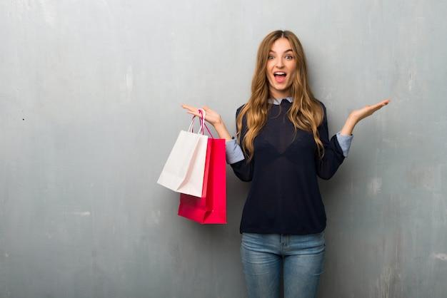 Meisje met boodschappentassen met verrassing en geschokt gelaatsuitdrukking