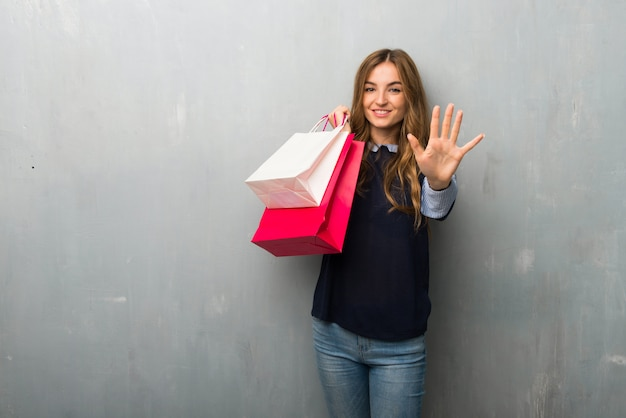 Meisje met boodschappentassen vijf met vingers tellen