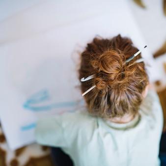 Meisje met borstel in haren die op papier schilderen en op vloer zitten
