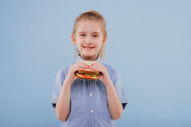 Meisje met boterham in de hand meisje kijkt naar de camera geïsoleerd op blauwe achtergrond kopie ruimte