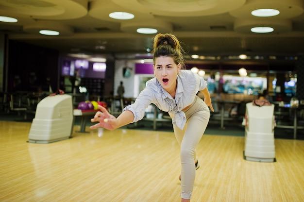 Meisje met bowlingbal op steeg gespeeld in bowlingclub.