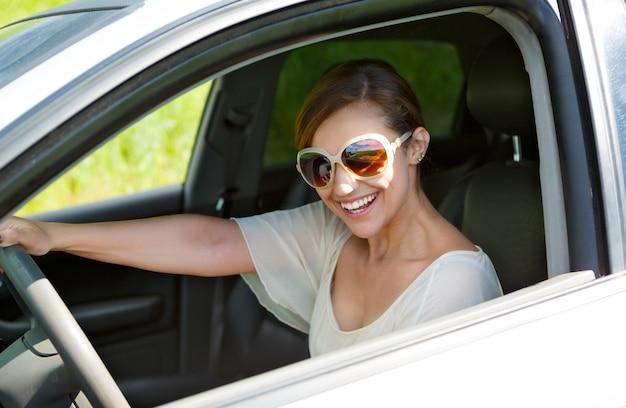 Meisje met bril achter het stuur van een auto