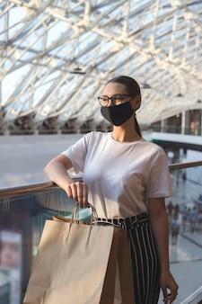 Meisje met bril en een beschermend masker in een winkelcentrum met aankopen