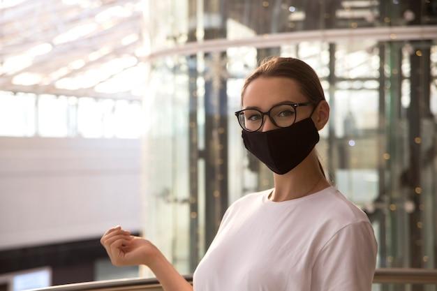 Meisje met bril en een beschermend masker in winkelcentrum