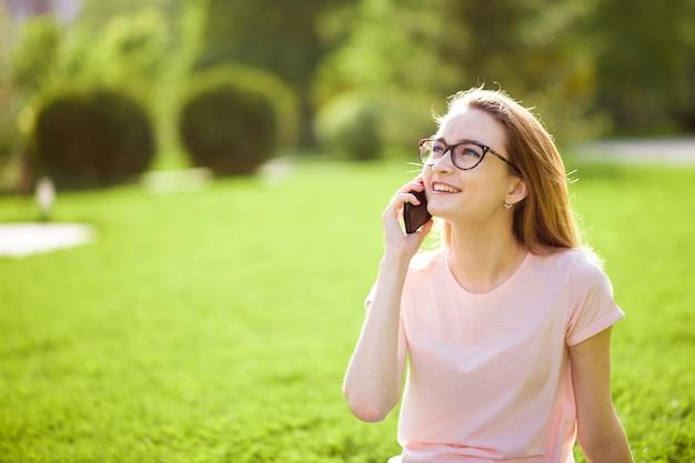 Meisje met bril praten aan de telefoon buitenshuis. kopieer ruimte.