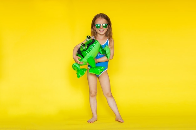 Meisje met bruin haar in blauwe zwembroek poseren op gele achtergrond