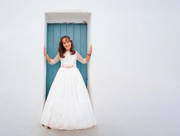 Meisje met bruin haar, leunend tegen een blauwe deur in een jurk. kopieer de ruimte.