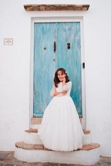 Meisje met bruin haar, leunend tegen een blauwe deur in een jurk