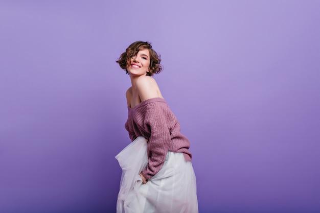 Meisje met bruin kort haar dat met belangstelling kijkt en met witte rok speelt. sensuele jonge vrouw draagt gebreide trui dromerig poseren in de buurt van paarse muur.