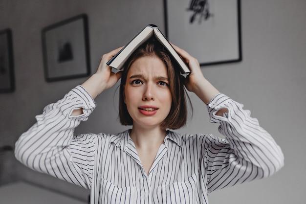 Meisje met bruine ogen legt boek op haar hoofd en kijkt verbijsterd en bang naar de camera.
