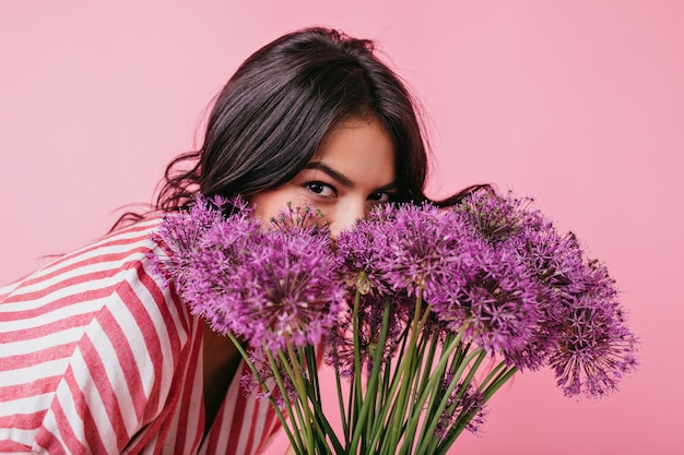 Meisje met bruine ogen verbergt zich achter grote paarse bloemen. portret van dame die pret heeft.