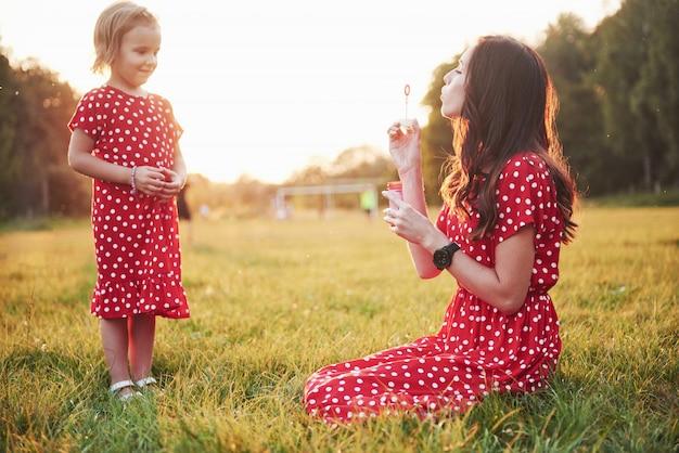 Meisje met bubbels met haar moeder in het park bij zonsondergang.