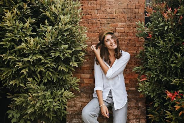 Meisje met charmante kuiltjesglimlachen. vrouw in trendy resort shirt en broek poseren ontspannen op bakstenen ruimte met struiken.