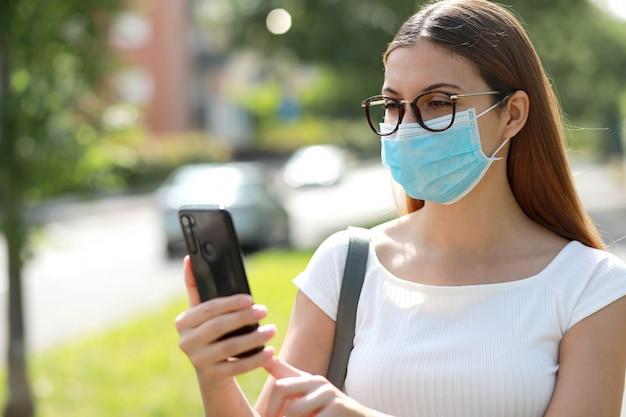 Meisje met chirurgisch masker en witte jurk typen op slimme telefoon in de straat van de stad