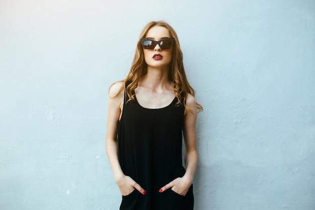 Meisje met de handen in de broek poseren met een zonnebril