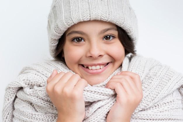 Meisje met dikke nekdoek en hoed glimlachen