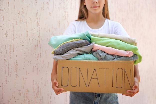 Meisje met donatiebox met zomerkleren.