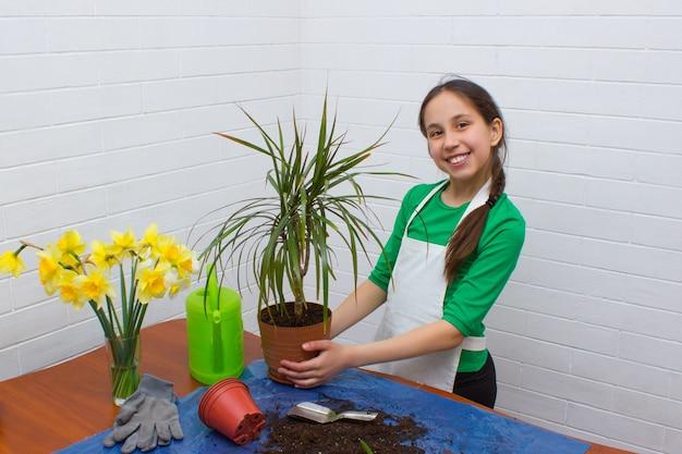 Meisje met donker haar en een schort doet thuis bloementeelt met een bloempot in haar handen