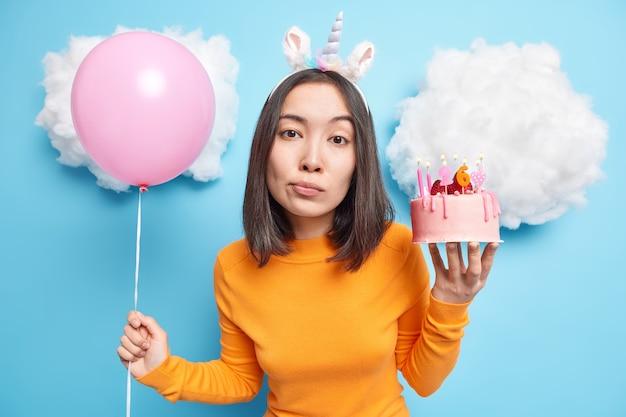 Meisje met donker haar houdt heerlijke aardbeientaart vast en opgeblazen ballon kijkt kalm naar de camera draagt vrijetijdskleding geïsoleerd op blauw