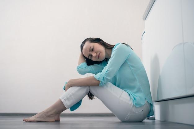 Meisje met donker haar zittend op de vloer in de kamer, houdt zijn hoofd en huilen, verdriet van afscheid, het einde van de relatie