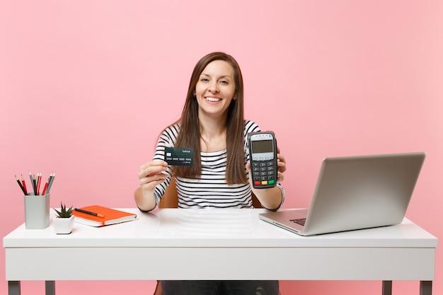 Meisje met draadloze moderne bankbetaalterminal om creditcardbetalingen te verwerken en te verwerven, werkt aan een bureau met pc-laptop geïsoleerd op roze achtergrond. prestatie zakelijke carrière concept. ruimte kopiëren.