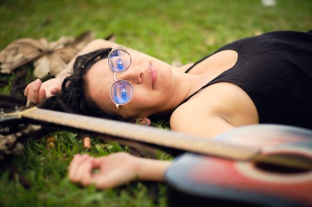 Meisje met dreadlocks liggend op de groene weide met haar gitaar opzij en wat droge bladeren om haar heen.