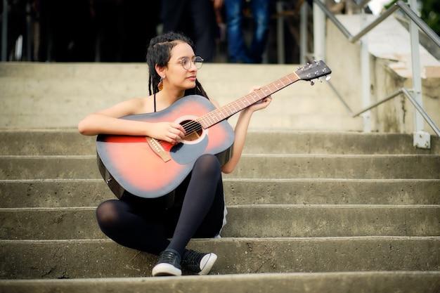 Meisje met dreadlocks meisje en bril zittend op de trap gitaar spelen terwijl mensen om haar heen lopen.