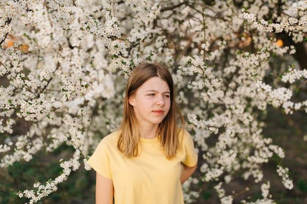 Meisje met droevig gezicht, pijnlijke rug. klein meisje in lentetuin. corona-epidemie