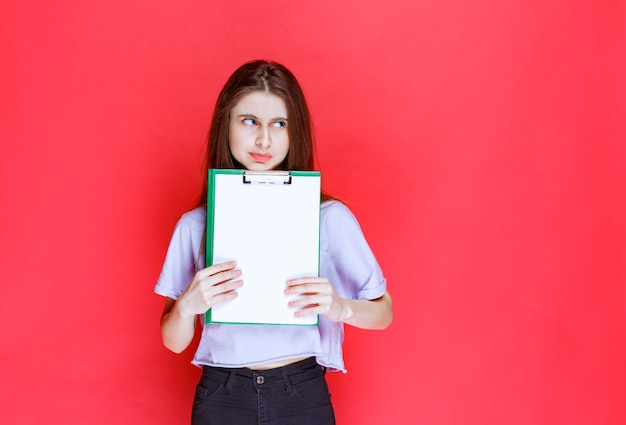 Meisje met een blanco rapportageblad en denken.