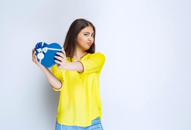Meisje met een blauwe geschenkdoos in de vorm van een hart die het terugstuurt omdat ze er niet van genoot.