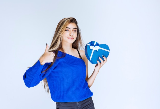 Meisje met een blauwe hartvormige geschenkdoos die zich positief en tevreden voelt.
