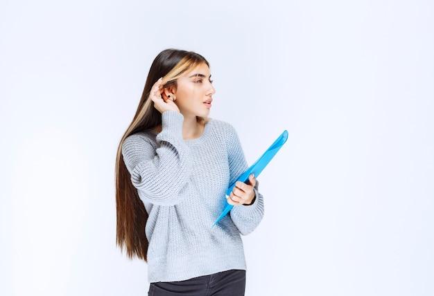 Meisje met een blauwe map die een oor opent om goed te luisteren.