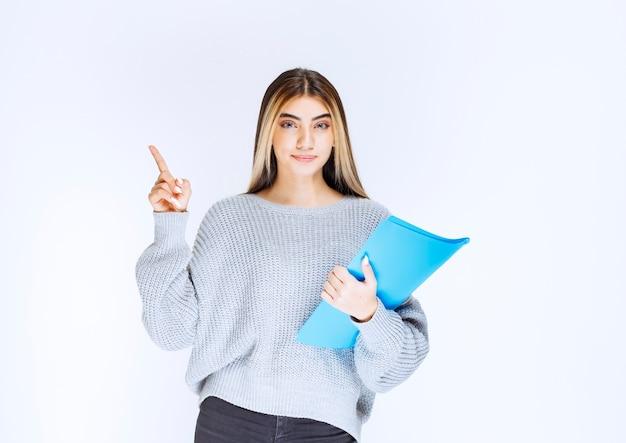 Meisje met een blauwe map die naar iemand opzij wijst.