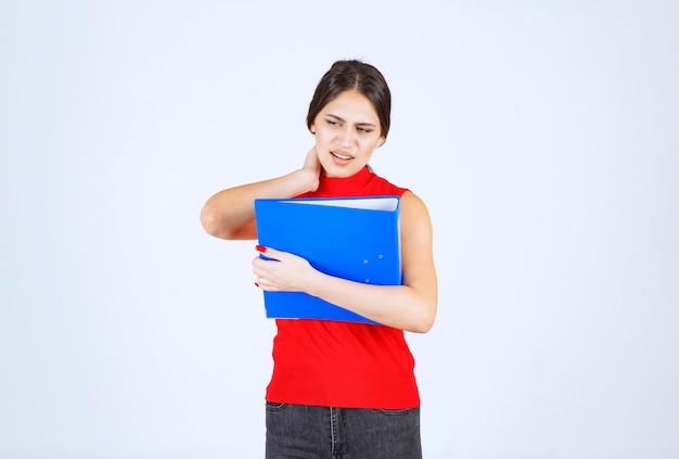Meisje met een blauwe map heeft hoofdpijn en nekpijn.