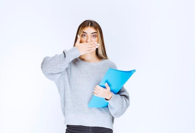 Meisje met een blauwe map kijkt verward en doodsbang.