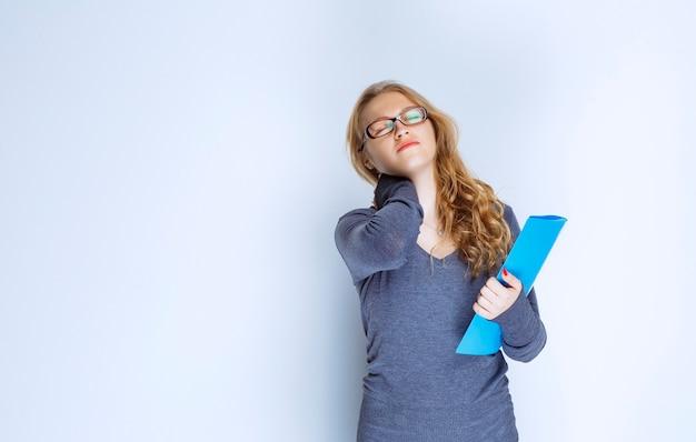Meisje met een blauwe map ziet er slaperig en moe uit.