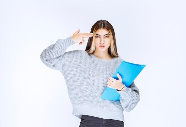 Meisje met een blauwe rapportmap en denken.
