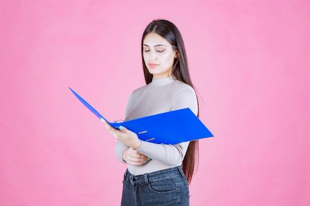 Meisje met een blauwe rapportmap en ziet er moe uit