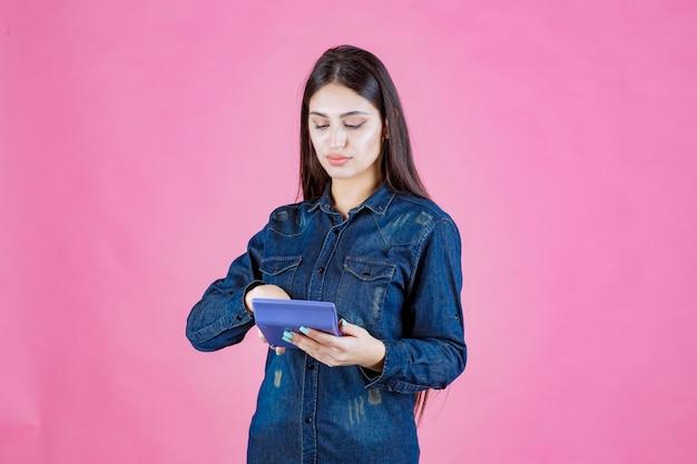 Meisje met een blauwe rekenmachine in de hand en het berekenen