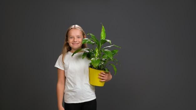 Meisje met een bloemplant in gele kleur pot in haar handen