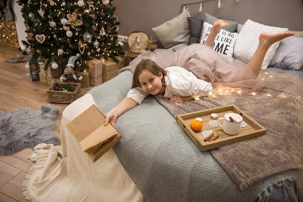 Meisje met een boek dat in bed ligt, ontbijt op bed, soft focus