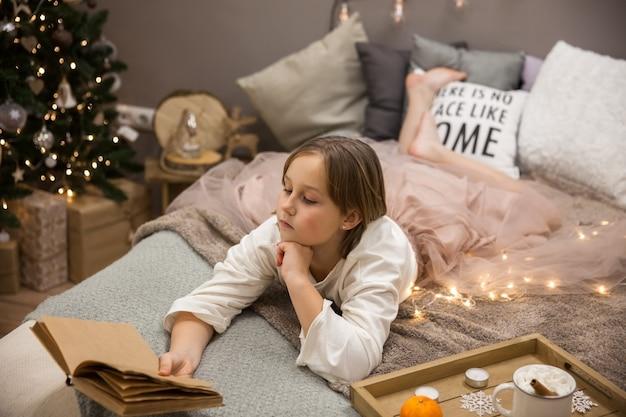 Meisje met een boek dat in bed ligt, ontbijt op bed