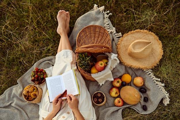 Meisje met een boek in haar handen die tijdens een picknick in openlucht op een zonnige dag ontspannen. bovenaanzicht.