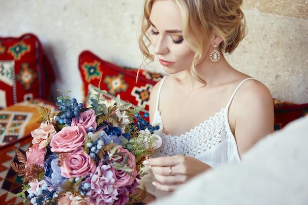 Meisje met een boeket bloemen in haar handen wacht op haar geliefde man in de buurt van het huis. perfect kapsel, krullend haar. liefdesverhaal