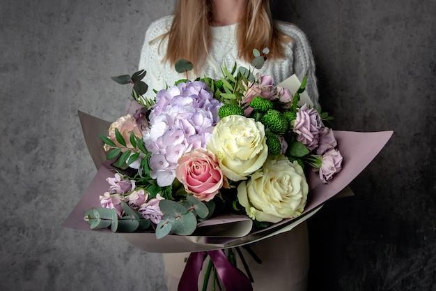 Meisje met een boeket bloemen tegen de muur