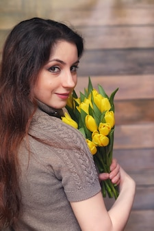 Meisje met een boeket gele tulpen. meisje met een geschenk van bloemen in een vaas. een cadeau voor meisjes op een vrouwelijke vakantie met gele tulpen op de vloer.