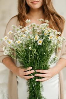 Meisje met een boeket madeliefjes, zomerbloemen in haar handen. zomer