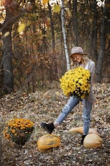 Meisje met een boeket van chrysanten en pompoenen in de herfst