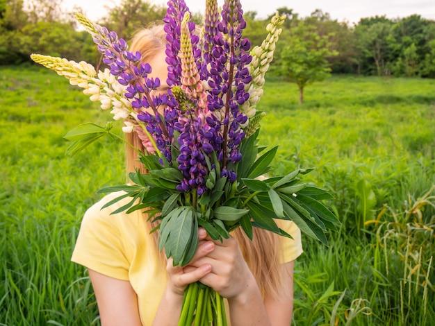 Meisje met een boeket van heldere bloemen in de hand.